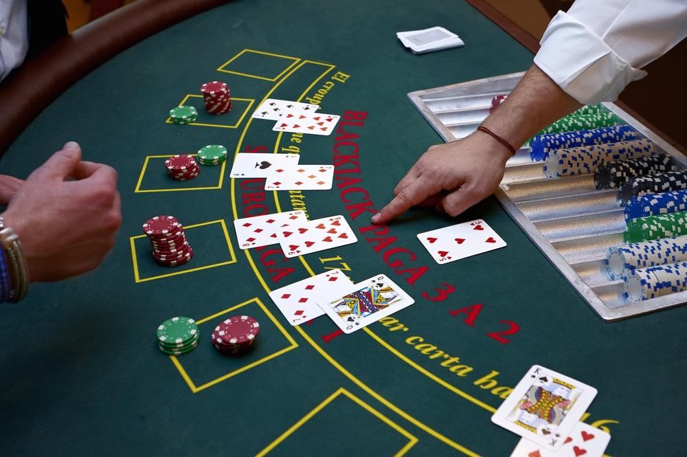 Blackjack-Spieltisch mit mehreren Spielern, offenen Karten und Einsätzen.